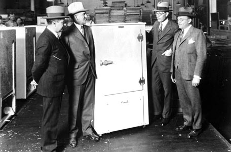 Old type refrigerator with 4 men around them
